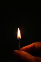Hand holding lighted match