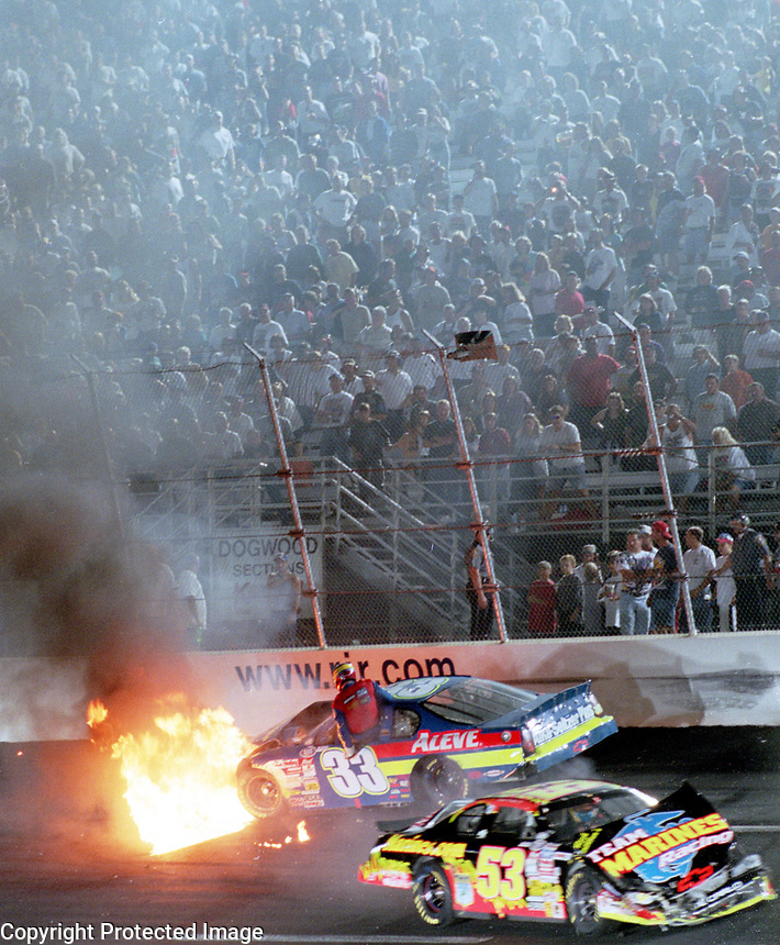 NASCAR driver Tony Raines climbs from his burning race car after crashing with Hank Parler Jr. (#53) during a Busch Series race at Richmond, VA on Friday, 9/8/00.  (Photo by Brian Cleary)