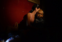 Mother and her child hiding in an old Soviet Union bomb shelter during shelling. Donetsk, Eastern Ukraine. October 14, 2014