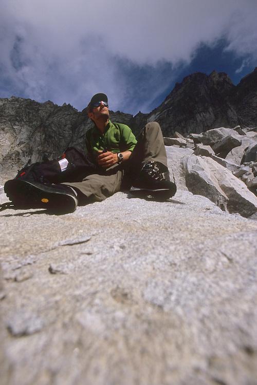 Pausing on a granite boulder underneath Cacciabella Pass (2800 m). Bergell, Switzerland, August 2011.