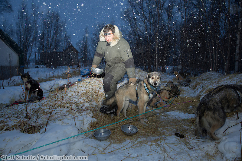 Michael Suprenant feeds his dogs duirng a light snowfall at the halfway checkpoint of Iditarod on Saturday March 9, 2013...Iditarod Sled Dog Race 2013..Photo by Jeff Schultz copyright 2013 DO NOT REPRODUCE WITHOUT PERMISSION