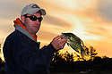00247-011.10  Black Crappie: Angler displays crappie while silhouetted against a low sun.  Panfish, fishing, lake, river.