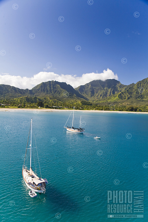 Cruising sailboats in Hanalei Bay with Namolokama Mountain in the background