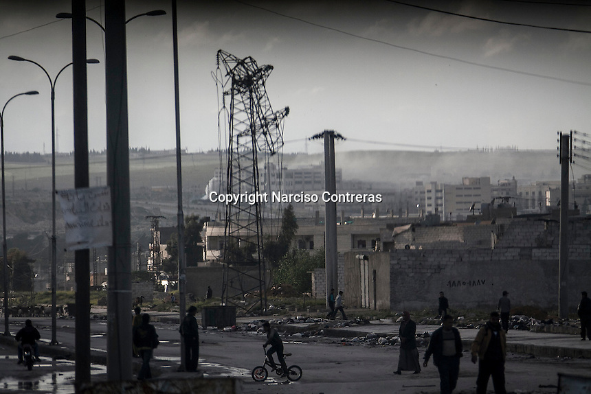 Syrian residents walk along a street damage in Hananu district as smoke rises from the battlefield in Kindi district, at the bottom, due the heavy fighting between rebel fighters and troops loyal to President Bashar Al-Assad in Aleppo, Syria.