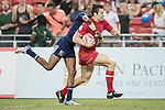 Perry Baker of USA tries to tackle Matt Mullins of Canada, who runs with the ball during the match United States vs Canada, the Cup Final of the HSBC Singapore Rugby Sevens as part of the World Rugby HSBC World Rugby Sevens Series 2016-17 at the National Stadium on 16 April 2017 in Singapore. Photo by Victor Fraile / Power Sport Images