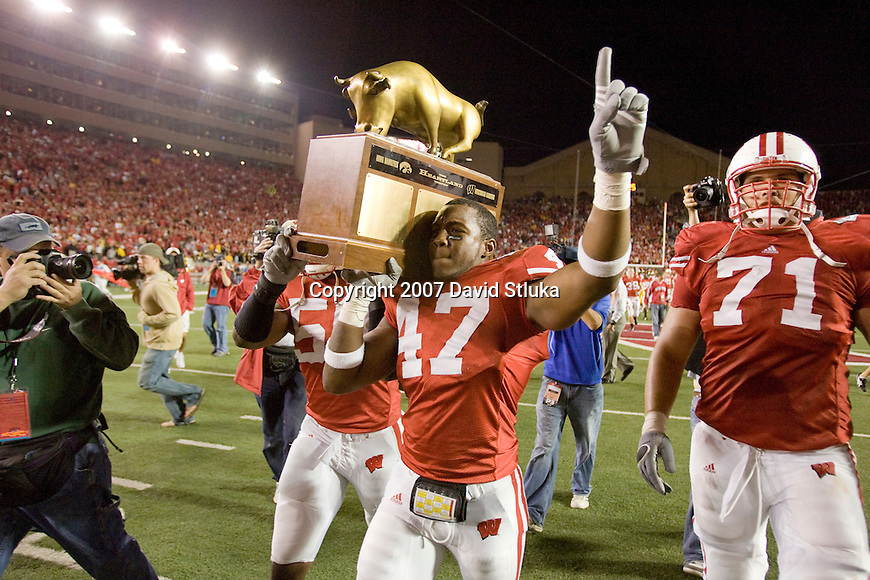MADISON, WI - SEPTEMBER 22: O'Brien Schofield #50 and Jaevery McFadden #47 of the Wisconsin Badgers carry the Heartland Trophy off the field after the game against the Iowa Hawkeyes at Camp Randall Stadium on September 22, 2007 in Madison, Wisconsin. The Badgers beat the Hawkeyes 17-13. (Photo by David Stluka)