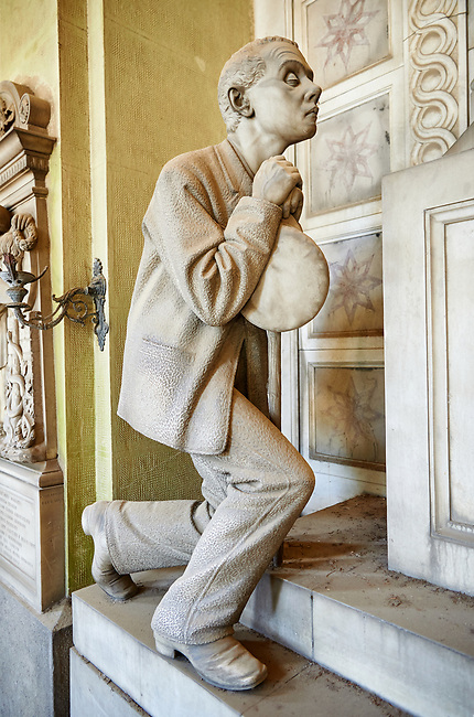 Picture and image of the Realistic blind man stone funary monument sculpture commissioned by Enrico Amerigo for his sisters memory. beside the pedestal on which the sculptor set the deceased's bust he placed, on the left, the figure of an old blind man, kneeling down and leaning on a stick; on the right he placed the figure of a young orphan girl, recognizable as such by her kindergarten uniform, portrayed in the act of making the sign of the cross. This work belongs to the Realism, a trend which was typical during the 1880s and 1890s, according to which the orphans, the poor, the sick and all those who benefited from somebody's generosity had to be portrayed in a concrete fashion. Sculptor G Moreno 1890. Section A, no 53, The Staglieno Monumental Cemetery, Genoa, Italy