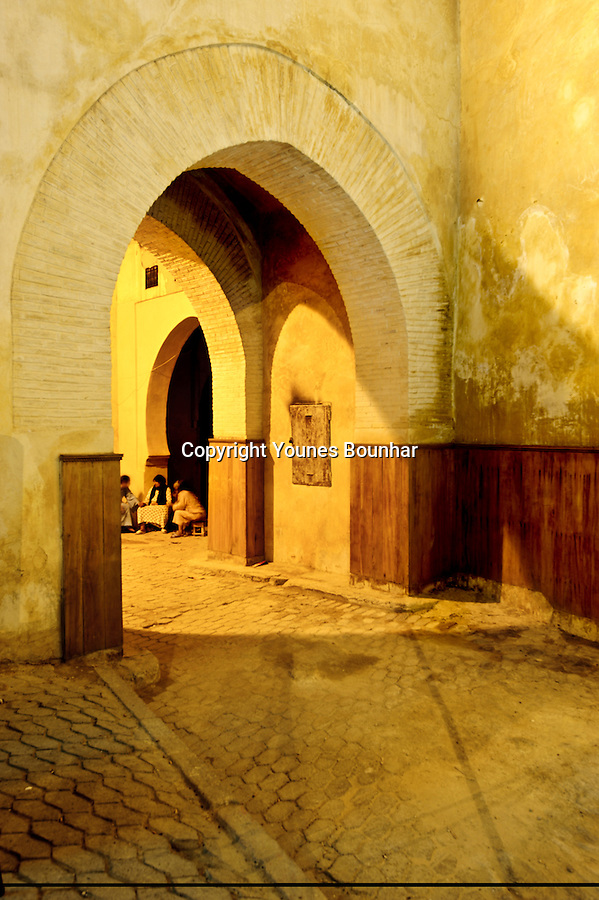 Three women engrossed in a riveting conversation in an archway under bab boujloud, one of the main entrance to the old medina of Fez