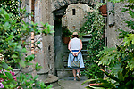 An arched pathway between houses in the Italian town of Castello, a town built on the remains of an old castle on the hills surrounding Lake Lugano. A women walks on an arched pathway between houses in the Italian town of Castello, a town built on the remains of an old castle on the hills surrounding Lake Lugano