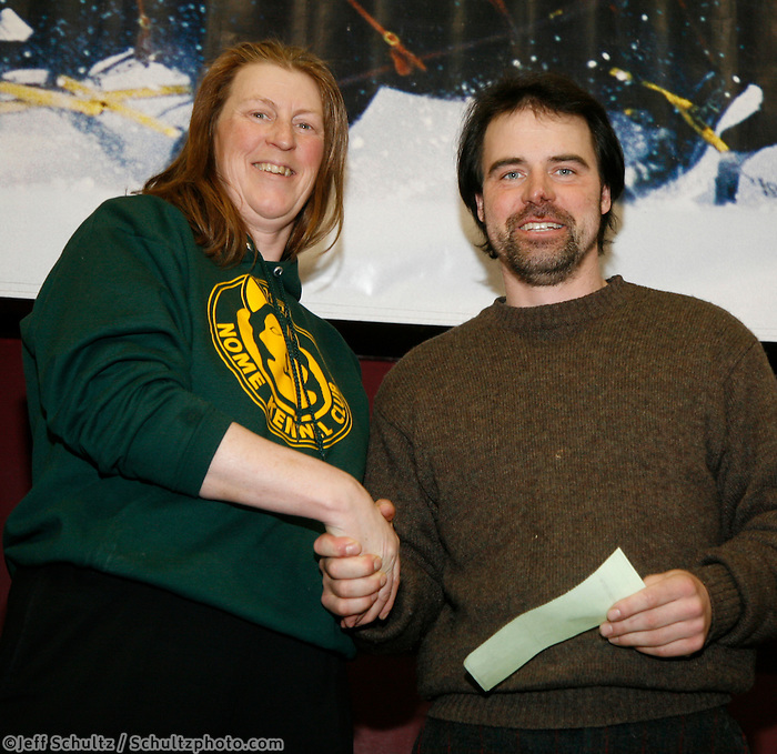 Cim Smyth recieves the fastest time from Safety to Nome award from Kirsten Bey at the Nome awards banquet.