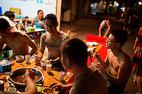 People eat hotpot at a streetside restaurant on Tiyu Road in central Yuzhong district, Chongqing, China. Tiyu Road is lined by streetside shaokao and hotpot restaurants.