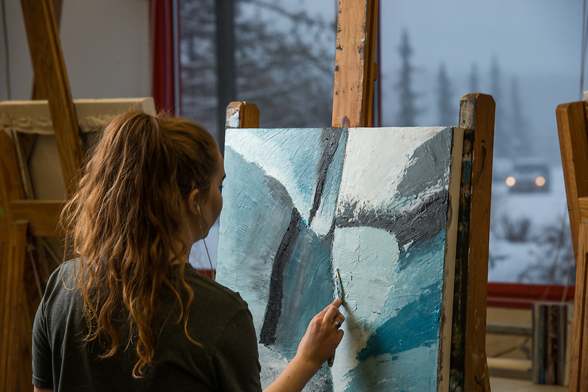 Anya Toelle paints during Professor Tom Chung's Intermediate Painting (ART A313) class in UAA's Fine Arts Building.