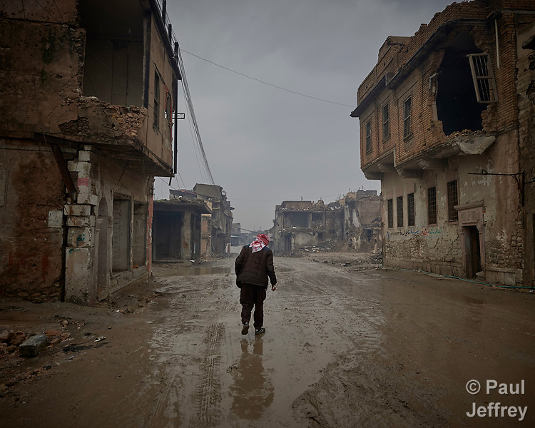 Qasim Yahia Ali, 75, walks along a rainy street in the old city of Mosul, Iraq. His house was destroyed during the 2017 Battle of Mosul, which led to the defeat of the Islamic State group, also known as ISIS. During control of the city by the Islamic State, he earned money by making clandestine liquor. In the wake of the war, he has moved back into the old city and lives in the ruins.