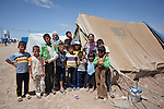 40 year old Hadia Oso Dawed (back row second from right), a Syrian refugee, stands outside her tent with her extended at the Domiz Refugee Camp in Iraqi-Kurdistan. Originally from Hassaka province in Syria, Hadia crossed the border into Iraq in February 2013 when shelling in near her home became heavier and she and her husband could no longer provide food or safety for their 5 children. The camp, run by the UNHCR and International Rescue Committee, is home to around 4,500 refugees who have fled from the ongoing Syrian civil war with up to 400 new inhabitants arriving every day.  Built on the site of a former Iraqi Army base that was bombed during the 2003 Coalition forces invasion of Iraq, the camp was cleared of cluster bombs and unexploded ordnance by the Mines Advisory Group (MAG), a demining NGO working in Iraqi-Kurdistan.