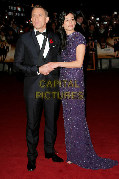 "DANIEL CRAIG & SATSUKI MITCHELL.The Royal World Premiere of ""Quantum Of Solace"" at the Odeon Leicester Square, London, England..October 29th 2008.James Bond full length black tuxedo jacket bow tie purple sparkly dress sling couple holding hands .CAP/AH.©Adam Houghton/Capital Pictures."