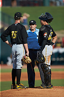 Home plate umpire Josh Gilreath and West Virginia Power catcher Deon Stafford (22) check on starting pitcher Travis MacGregor (15) after he was hit with a batted ball during the game against the Greensboro Grasshoppers at First National Bank Field on August 9, 2018 in Greensboro, North Carolina. The Power defeated the Grasshoppers 5-3 in game one of a double-header. (Brian Westerholt/Four Seam Images)