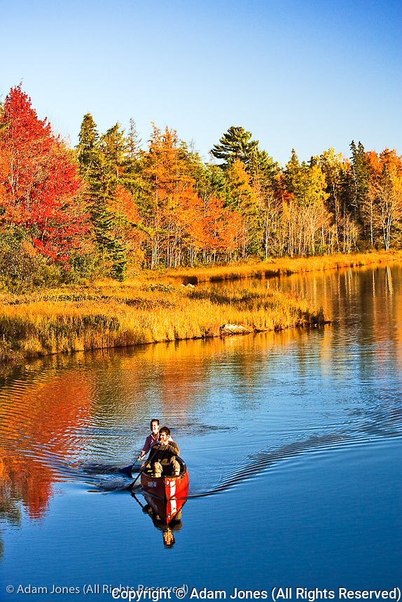 Two people enjoying autumn canoeing on small stream, Bass Harbor, Maine