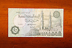 Egyptian 50 Piastres currency note on table with Arabic script and mosque