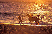 Woman walking alongsidea horse off sunset beach, Oahu