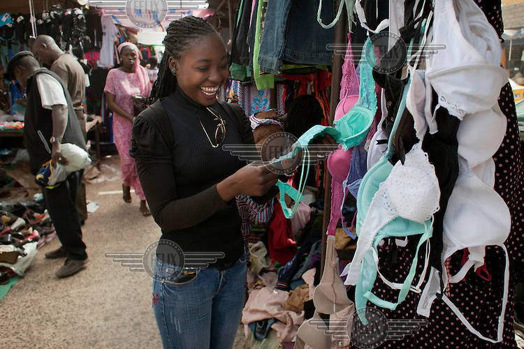 Mami (Madijiguene Ndiaye) purchases a turquoise bra (originally donated by Charlotte Eagar) from trader Ndeye Faye at the weekly market in Dakar. Bras are in particular high demand in Senegal as the item of clothing that traders can get the most money for and Oxfam are launching a campaign, The Big Bra Hunt to encourage more people in the UK to donate to their shops.