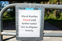 Warning posted on fencing surrounding an alligator mound. Photographed at Arthur Marshall Loxahatchee Wildlife Refuge, Boynton Beach, Florida.