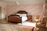 A guest bedroom features a toile de Jouy wallpaper and is furnished with a French wicker bed