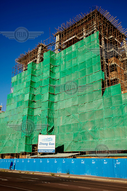A building, under construction in the new Central Business District, is covered with a green hording. The firm constructing the building is Chinese.