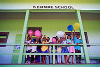 Elementary school students holding balloons on the porch of Keanae School