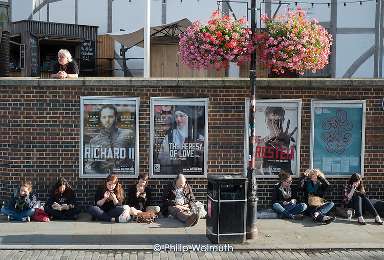 Tourists queueing outside The Globe Theatre London South Bank