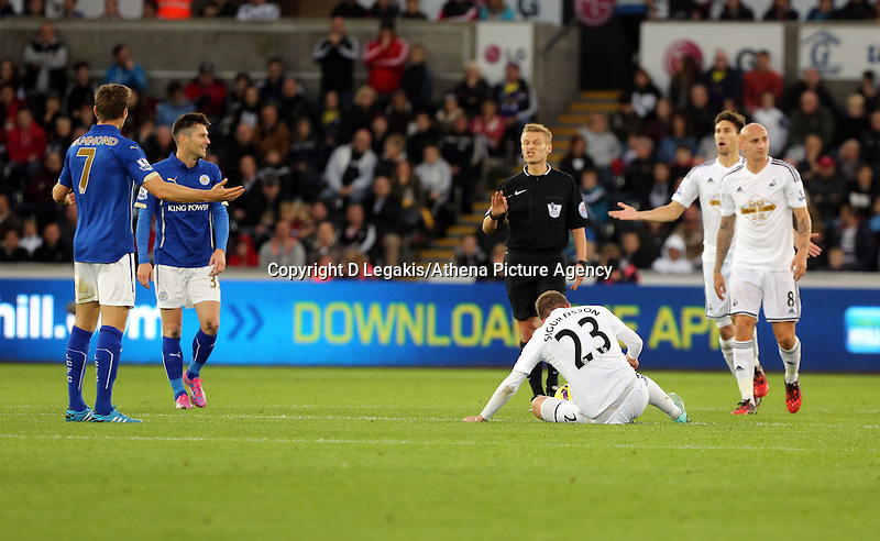Pictured: Gylfi Sigurdsson of Swansea on the ground, Dean Hammond of Leicester (L) is protesting to match referee M Jones<br /> Saturday 25 October 2014<br /> Re: Barclays Premier League, Swansea City FC v Leicester City at the Liberty Stadium, south Wales, UK