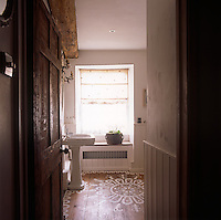 A view through an open door to a pedestal washbasin in a traditonal bathroom with a painted wooden floor.