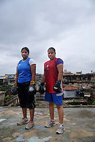 INDIA (West Bengal - Calcutta)July 2010,Shakila Babe(left) and Sanno Babe (right) standing on the roof of their house during practice. Shakila and Shanno are twins from a poor muslim family of Iqbalpur, Kolkata. . Inspite of their late father's unwillingness to send his daughters to take up  boxing her mother Banno Begum inspired them to take up boxing at the age of 3. Their father was more concerned about the social stigma they have in their community regarding women coming into sports or doing anything which may show disrespect to the religious emotions of his community. Shakila now has been recognised as one of the best young woman boxers of the country after she won the  international championship at Turkey in the junior category. Shanno is also been called for the National camp this year. Presently Shakila and shanno has become the role model in the Iqbalpur area  and parents from muslim community of Iqbalpur have started showing interst in boxing. Iqbalpur is a poor muslim dominated area mostly covered with shanty town with all odds which comes along with poverty and lack of education. - Arindam Mukherjee