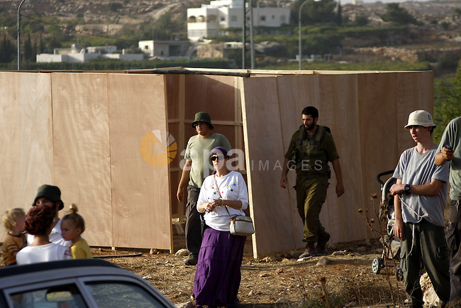 Jewish settlers stand outside a wooden structure built to mark the end of a 10-month ban on settlement construction, on September 26, 2010, near the Israeli settlement of Kiryat Arba outside the West Bank town of Hebron. Photo by Mamoun Wazwaz