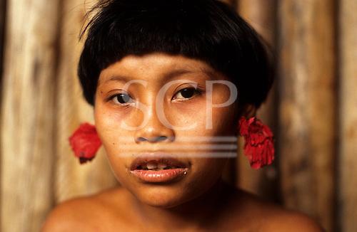 Roraima, Brazil. Yanomami teenage girl with red flower ear plugs.