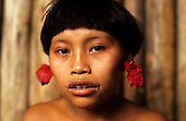 Roraima, Brazil. Yanomami teenage girl with red flower ear plugs.