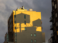 Shadows of ubiquitous New York rooftop water tanks on the side of a building at sunset on Sunday, January 10, 2015.  (© Richard B. Levine)