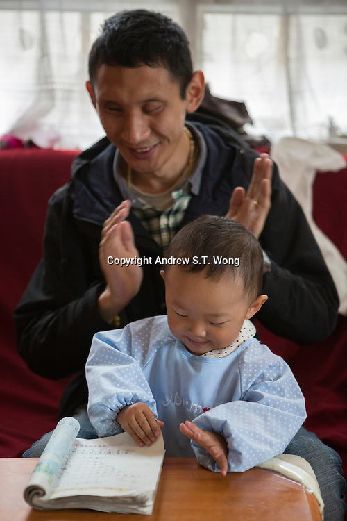 Blind Tibetan Headmaster Nyima Wangdu of the School for the Blind In Tibet plays with his daughter Tenzin Dichen at home inside the campus in the capital city of Lhasa, September 2016.