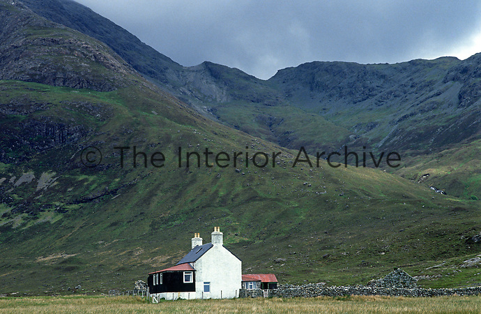 The Cuillin Mountains tower above the isolated fishing lodge at Camasunary Bay on the Isle of Skye
