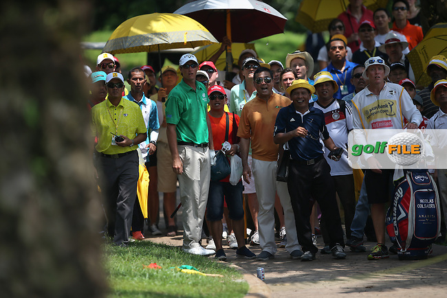 Nicolas Colsaerts (BEL) finds trouble on the 17th in the trees and amongst the gallery during Round Three of the 2014 Maybank Malaysian Open at the Kuala Lumpur Golf & Country Club, Kuala Lumpur, Malaysia. Picture:  David Lloyd / www.golffile.ie