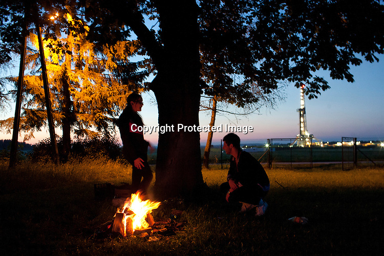 Young inhabitant of Szalenik village sits by the fire.  The rig site in Szalenik operated by the Polish Gas and Oil company (PGNiG) was constructed as a shale gas test drilling site. The inhabitants like the night view of the drilling rig. They say the illuminated structure looks like a spaceship to them.