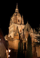 Low angle view of Cathedral, Salamanca, Spain, pictured at night, floodlit, on December 17, 2010. Features visble are the Torrre de Gallo and the Cupola. The scallop-tiled  Torre del Gallo (Cock Tower) is a ribbed umbrella lantern in the Byzantine style. Salamanca, Spain's most important University city,  has two adjoining Cathedrals, Old and New. The old Romanesque Cathedral was begun in the 12th century, and the new in the 16th century. Its style was designed to be Gothic rather than Renaissance in keeping with its older neighbour, but building continued over several centuries and a Baroque cupola was added in the 18th century. Restoration was necessary after the great Lisbon earthquake, 1755. Picture by Manuel Cohen