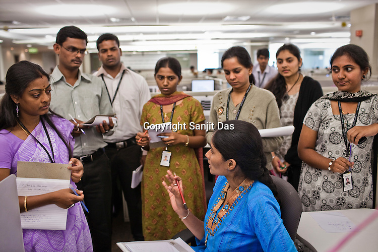Ernst & Young employees take notes from one of their senior colleagues at the Ernst & Young Global Shared Services office in Bangalore, Karnataka, India. Ernst & Young has 49% women working for them in the India office. Photo: Sanjit Das