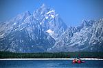 A young couple paddles a tandem sea kayak on Jackson Lake in Grand Teton National Park, Jackson Hole, Wyoming.