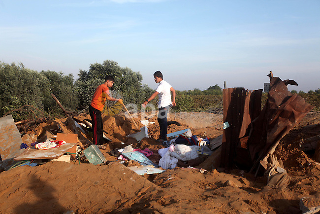 """Palestinians inspect the damage after an Israeli retaliatory air strike demolished the house of a Palestinian family on October 11, 2015 in the Zeitun sector south of Gaza City. A pregnant Palestinian mother and her toddler daughter were killed in the air strike while three others were still trapped under the home's ruins, medical sources said. Israel said it had targeted """"two Hamas weapon manufacturing facilities"""" in response to two rocket launches at Israel the day before. Photo by Ashraf Amra"""