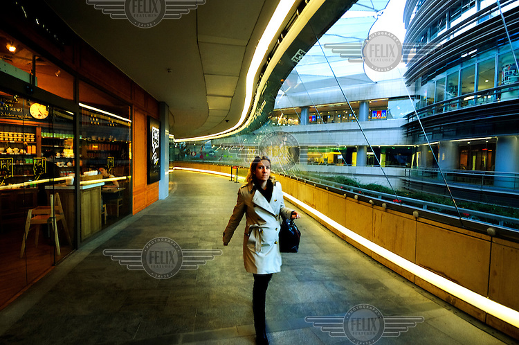 A young woman in Kanyon, a luxury shopping mall.  Its curved and semi open-air design has won several international awards.