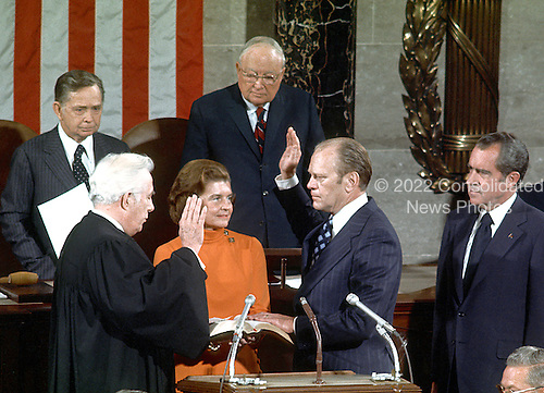 United States Representative Gerald R. Ford (Republican of Michigan) is sworn-in as Vice President of the United States in the United States House of Representatives chamber by Chief Justice Warren Burger on December 6, 1973.  His Wife, Betty, holds the family bible.  United States President Richard M. Nixon looks on from far right.   Speaker of the United States House of Representatives Carl Albert (Democrat of Oklahoma) looks on from the upper left.  United States Senator James O. Eastland (Democrat of Mississippi), the President pro-tempore of the United States Senate, looks on from the upper center.<br /> Credit: Arnie Sachs / CNP