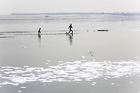 Children run through the shallows of the Ganges River. Waste water in the foreground from nearby tanneries has contributed to the severe degradation of local water resources near the city of Kanpur. The city is notorious for having some of the country's worst water pollution which is created by the local leathery tannery industry.