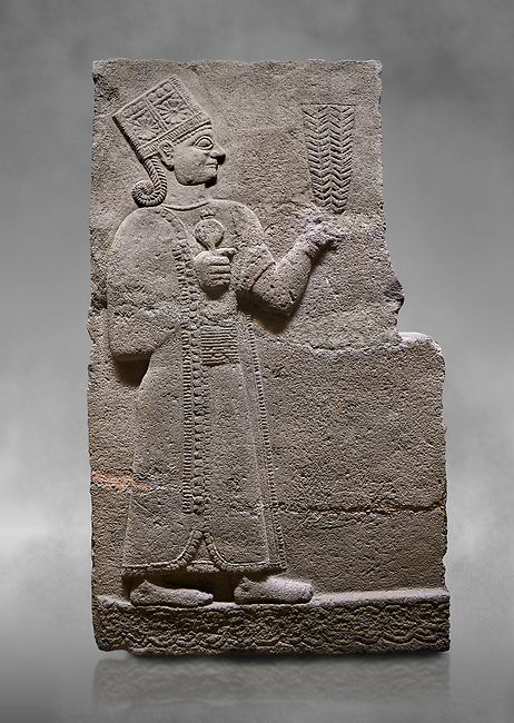 Hittite relief sculpted orthostat stone panel of Long Wall Basalt, Karkamıs, (Kargamıs), Carchemish (Karkemish), 900-700 B.C. Anatolian Civilisations Museum, Ankara, Turkey<br /> <br /> Goddess Kubaba. Goddess is depicted from the profile. She holds a pomegranate in her hands on her chest. She carries a one-horned headdress on her head. Her braided hair hangs down to her shoulder . <br /> <br /> On a grey art background.