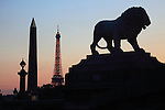 The twilight view of a statue of a lion and Obelisk in Concorde Square Place de la Concorde with Eiffel Tower in the background. Paris. France
