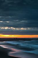 Sunset on Hokitika Beach with people fishing - South Westland, West Coast, New Zealand